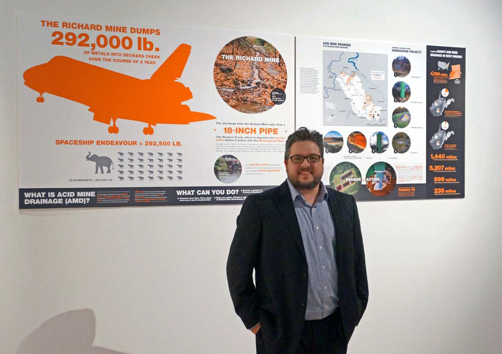 Forrest Conroy stands in front of one of the graphics that he created for FODC.